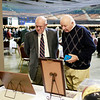 "Bob Gardner, left, and Robert ""Frog"" Young look over old photos of coach Dave Barksdale during the Spirit of Beckley Awards Monday at the Beckley-Raleigh County Convention Center. (Chris Jackson/The Register-Herald)"