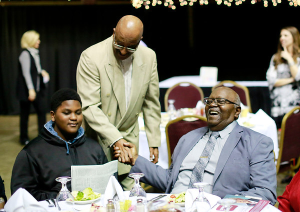 Beckley Councilman Frank Williams, standing left, shakes hands with Don Parker, right, as Trey Parker looks on during the Spirit of Beckley Awards Monday at the Beckley-Raleigh County Convention Center. (Chris Jackson/The Register-Herald)