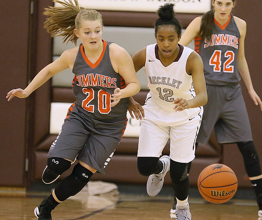 (Brad Davis/The Register-Herald) Summers County's Tiffani Cline rushes in to scoop up a loose ball after poking it loose from Woodrow Wilson's Lyric Moon Wednesday night in the Woodrow gym.