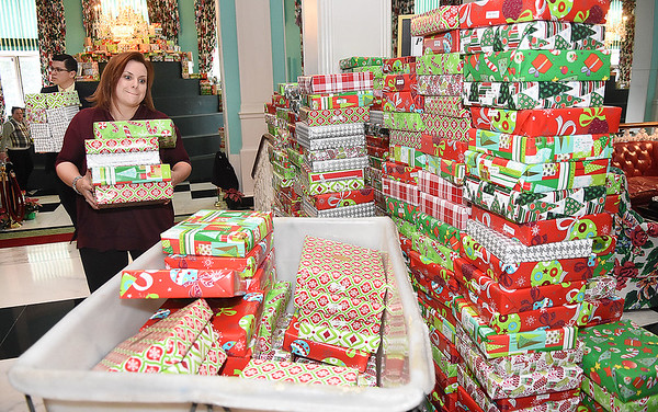 Amanda Cleghon, employee for The Greenbrier Resort, helps load up Christmas gifts for the Dream Tree for Children distribution.<br /> (Rick Barbero/The Register-Herald)
