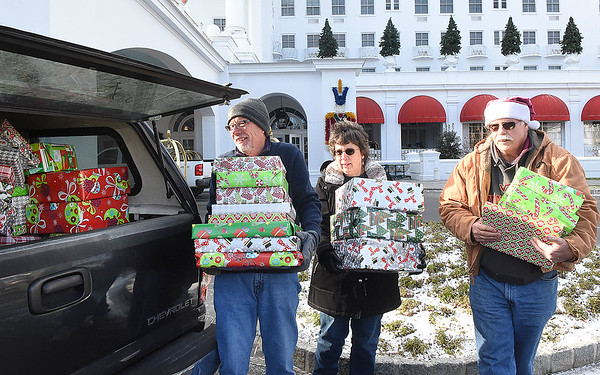 Jeff Delong, left, Ann Ford and Wes Ford, with Central United Methodist Church in Staunton, Va., carry gifts away during the Dream Tree Children distribution. The gifts will be distributed to childen at the church and Cub Run Elementary School in Penn Land, Va. <br /> (Rick Barbero/The Register-Herald)