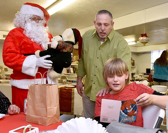 (Brad Davis/The Register-Herald) Dustin Vanoy, 13, receives a gift from Santa, who had a few more gifts to give during Sophia United Methodist Church's Community Christmas Dinner Sunday afternoon. Church member John Fanary, middle, looks over his special card with him.