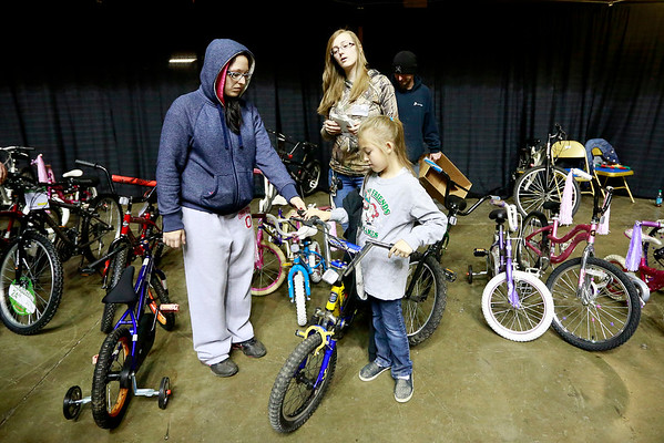 Volunteer Stephanie Hazelwood, 8, helps Natalie Todd, from Beckley, with a bike as volunteer Melissa Urciolo, from Beckley, helps too during the Mac's Toy Fund at the Beckley-Raleigh County Convention Center on Saturday. (Chris Jackson/The Register-Herald)