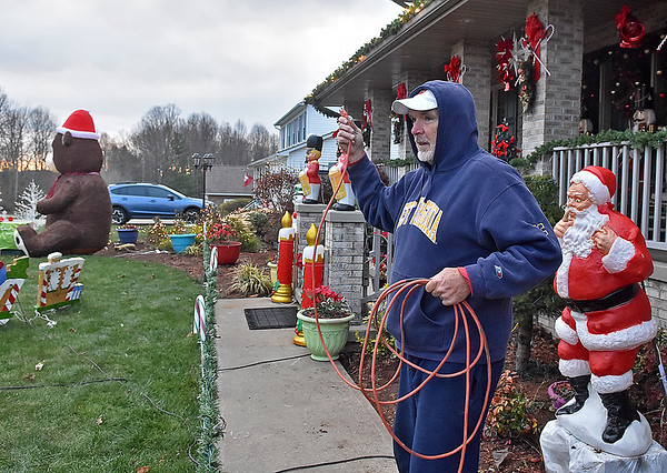 (Brad Davis/The Register-Herald) Area resident Walt Kiser arranges a slew of wires to power the Christmas wonderland that his front yard has morphed into at his Grandview Road home Friday afternoon. Kiser, a retired coal miner formerly from Oceana, has a history of decking out his yard for Christmas and has accumulated tons of excess decorations that he's currently letting go in a garage sale. He's been working on this one since November 6th and says this will probably be one of the last big setups he'll do. Just travel Grandview Road towards Shady Spring and you can't miss his Christmas wonderland.