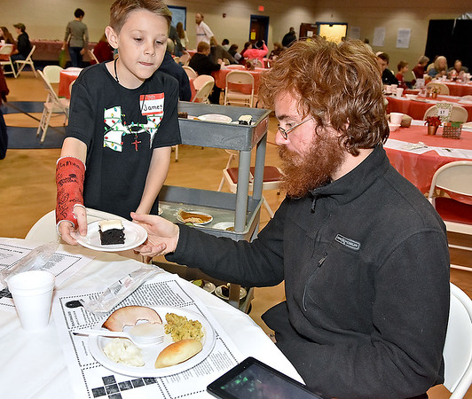 (Brad Davis/The Register-Herald) Young volunteer James Beebe gets a slice of cake for Beckley resident Patrick Milli as he makes his rounds with the dessert cart during United Methodist Temple's Community Christmas Dinner Sunday afternoon inside The Place.