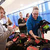 Tonia Lively, from Beckley, looks over mittens and gloves as volunteer Jessica Runion helps her during the Mac's Toy Fund at the Beckley-Raleigh County Convention Center on Saturday. (Chris Jackson/The Register-Herald)