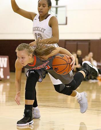 (Brad Davis/The Register-Herald) Summers County's Brittney Justice tries to keep her balance after rushing to scoop up a loose ball as Woodrow Wilson's Lyric Moon defends Wednesday night in the Woodrow gym.