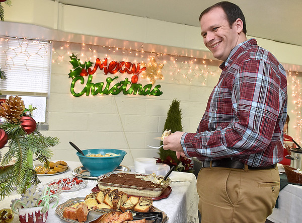 (Brad Davis/The Register-Herald) Brandon Rumberg notices the camera as he goes for dessert during Sophia United Methodist Church's Community Christmas Dinner Sunday afternoon.