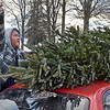 (Brad Davis/The Register-Herald) Oak Hill resident Joseph Rizer ties a fresh cut Christmas tree grown by Crickmer Farms in Danese to the top of his car after he and his wife Jeannie picked it out during holiday market hours Friday afternoon at the Rick Rutledge Pavilion. The pavilion is the site of a special Christmas market open for the holiday season with several area vendors selling locally crafted, grown and produced seasonal items every Friday, Saturday and Sunday from 1:00 p.m. to 6:00 p.m.