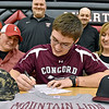 Liberty Raiders quarterback Hunter Wright signs on to play football at Concord University surrounded by his parents Larry and Jill, high school coaches (back row from left) Shannon Ross, Mark Workman, Glenn August and head coach Jeff Alexander along with siblings and other family members during a ceremony at the school Wednesday afternoon in Glen Daniel.