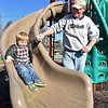 Two-year-old Grayson Redden makes his way down a slide with the help of his grandfather Cliff McGlophlin as the two take advantage of some sunny weather at the 2nd Street Park Wednesday afternoon.