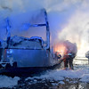 Smoke billows from a burned out utility trailer as Beaver Volunteer firefighters cut away sections with a circular saw to reach areas still burning Wednesday night along the Westbound lanes of Interstate 64 just past the Eisenhower Drive exit. The trailer belonged to FDH Velocitel, a company that builds and maintains broadcast and wireless towers, and was full of everything from electronic gear and antennas to winter clothing and climbing gear when it went up. The driver, Benjamin Ice, was hauling the trailer in a Ford pickup heading westbound towards the split with two other co-workers when he said another motorist drove up beside him and alerted them to the fire. The three then pulled off into the emergency lane, tried to use fire extinguishers they had in the truck, but the trailer was too fully engulfed for them to do any good.