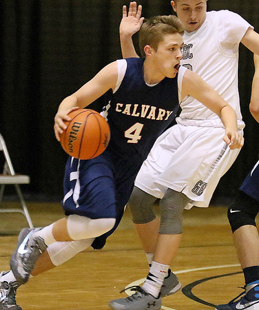 (Brad Davis/The Register-Herald) Calvary's Carson Taylor drives around Greater Beckley Christian's Devin Acord Thursday afternoon at the Beckley-Raleigh County Convention Center.