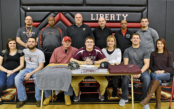 Liberty Raiders quarterback Hunter Wright signs on to play football at Concord University surrounded by his parents Larry and Jill, his high school coaches along with siblings and other family members during a ceremony at the school Wednesday afternoon in Glen Daniel.