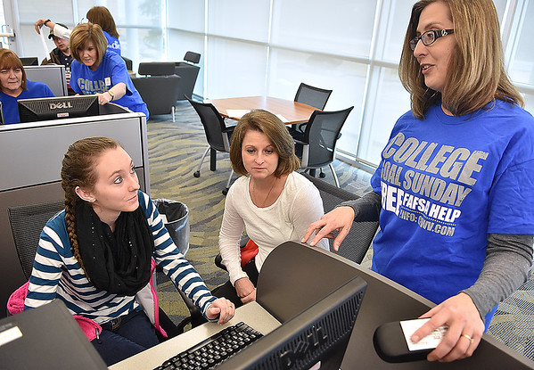 Independence High senior Karlee Hendrick and her mother Kim get help and advice filling out a FAFSA financial aid application online from educational outreach counselor Tammy Toney, right, during College Goal Sunday at the Erma Byrd Higher Education Center yesterday afternoon.