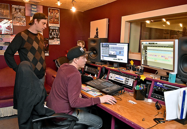(Brad Davis/The Register-Herald) Co-owners Jamie Smith, left, and Jason Lockart work in their recording studio with singer/songwriter Jenna Arthur (not photographed) as they record vocal tracks inside Kid in the Background Multimedia Factory February 17.