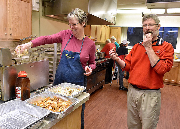 """Volunteer Kolleen Finch, left, gets a laugh out of fellow volunteer Mark Misco as he snacks on, or """"serves as quality control"""" as he called it, some of the fresh fried potato chips and shrimp she prepared, during the first of St. Francis de Sales Catholic Church's annual six-week fish fry in observance of Lent Friday night."""