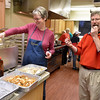 "Volunteer Kolleen Finch, left, gets a laugh out of fellow volunteer Mark Misco as he snacks on, or ""serves as quality control"" as he called it, some of the fresh fried potato chips and shrimp she prepared, during the first of St. Francis de Sales Catholic Church's annual six-week fish fry in observance of Lent Friday night."