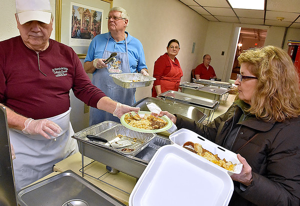 "Beckley resident and church member Sharon Fuerst, right, fills a couple of plates with help of volunteer servers (from left) John Romanchak, Larry Farley and Sheila Zeto during St. Francis de Sales Catholic Church's weekly Fish Fry Friday night. Fellow volunteer Sande ""Bear"" Genung, background by the door, looks on. The South Oakwood Avenue church will be serving dinner in observance of Lent every Friday for the next five weeks leading up to Easter."
