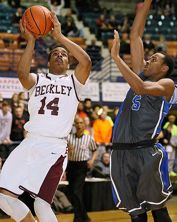 Woodrow Wilson's Malyk Fowlkes drives to the basket against Capital defender Kalik Ross during the Flying Eagles' loss to the Cougars Wednesday night at the Beckley-Raleigh County Convention Center.