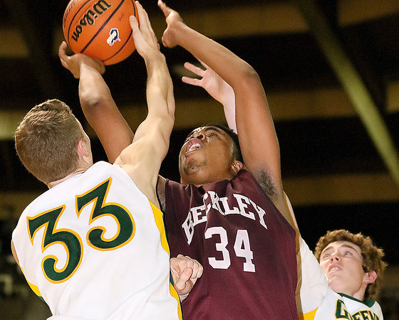 Woodrow Wilson's Brenton Walton drives and scores as Greenbrier East's Levi Massey, left, and Logan Taylor defend during the class AAA championship game Saturday night at the Beckley-Raleigh County Convention Center.