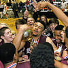 Woodrow Wilson's Tarek Payne embraces the trophy as he's mobbed by teammates and students after defeating Greenbrier East to take the Big Atlantic Classic class AAA championship Saturday night at the Beckley-Raleigh County Convention Center.