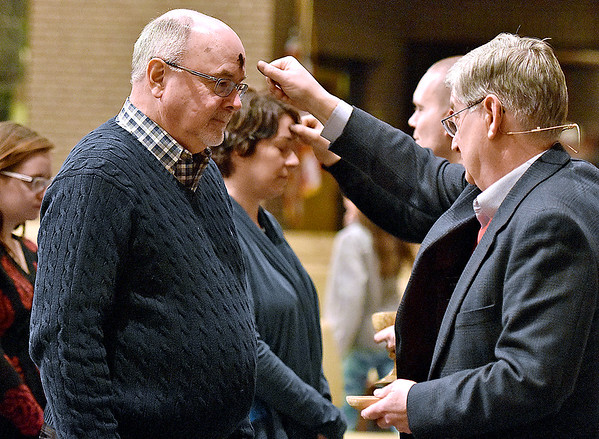 Pastors Randy Adkins, near, and Adam Justice, background, draw crosses on the foreheads of congregants as they take part in the imposition of ashes portion of Ash Wednesday services at United Methodist Temple last night. Ash Wednesday is day one of Lent's 40-day (Monday through Saturday) journey to Easter Sunday.