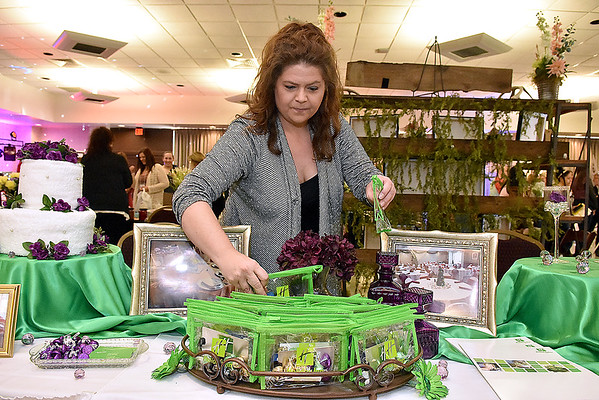 (Brad Davis/The Register-Herald) Director of Sales Rebecca Bailey keeps the table stocked with goody bags at the Holiday Inn vendor booth during the Bridal, Prom and Special Occasions Fair Saturday afternoon at the Beckley-Raleigh County Convention Center.