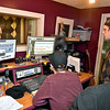 (Brad Davis/The Register-Herald) Co-owners Jamie Smith, left, and Jason Lockart work in their recording studio with singer/songwriter Jenna Arthur, visible through the window at left, as they record vocal tracks inside Kid in the Background Multimedia Factory February 17.