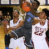 **Brad Davis/The Register-Herald**<br /> Capital's Kerry Martin rushes in between Woodrow Wilson's Nequan Carrington, left, and Isaiah Francis to earn an offensive rebound during the Flying Eagles' loss to the Cougars Wednesday night at the Beckley-Raleigh County Convention Center.
