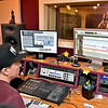 (Brad Davis/The Register-Herald) Co-owner Jamie Smith works in the recording studio with singer/songwriter Jenna Arthur as they record vocal tracks inside Kid in the Background Multimedia Factory February 17.