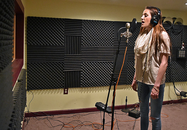 (Brad Davis/The Register-Herald) Singer/songwriter Jenna Arthur, one of their clients, records vocal tracks inside Kid in the Background Multimedia Factory's recording studio February 17.