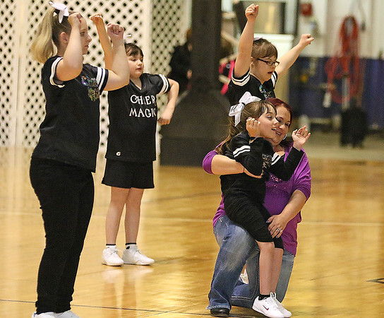 Brad Davis/The Register-Herald<br /> 11-year-old Alexis Martin (front) sits against Toni Daniel's leg as she leads her Cheer Magic Sparklers teammates Baylee Parkulo (far left), 18, Debra Butcher (background middle), 10, and Olivia Miller (background behind Martin and Daniel), 14, among others unphotographed in a routine Friday night at the Beckley-Raleigh County Convention Center. The Cheer Magic Sparklers are an all-ages, special needs cheerleading squad and they performed a special routine for the crowd during the halftime break of the Girls class AAA championship game between Morgantown and Greenbrier East.