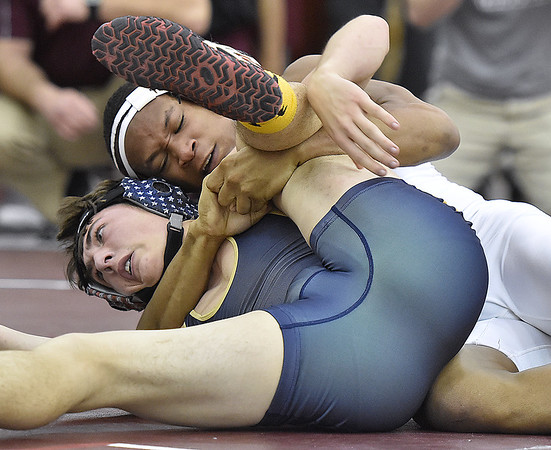 Woodrow Wilson's Leland Swafford (top) takes on Shady Spring's Chase DeMoss in 145-pound weight class matchup during the region three class AAA championships Saturday afternoon at Woodrow Wilson High School.