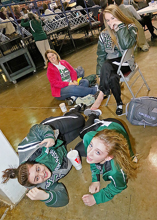 Brad Davis/The Register-Herald<br /> Wyoming East's Gabby Lupardus, upper right, chuckles as teammates Allie Lusk, lower left, and Misa Quesenberry, lower right, are suprised by the camera while they chill out prior to the #1 (class AA) Lady Warriors' game against fellow undefeated and #1 (class AAA) Morgantown Thursday night at the Beckley-Raleigh County Convention Center. Lupardus and her mother Paula (upper left) were working on stretching out the point guard's sprained ankle while Lusk and Quesenberry relaxed at the floor level with them.