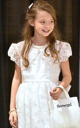 (Brad Davis/The Register-Herald) A young model shows off a flower girl dress during the fashion show portion of the Bridal, Prom and Special Occasions Fair Saturday afternoon at the Beckley-Raleigh County Convention Center.