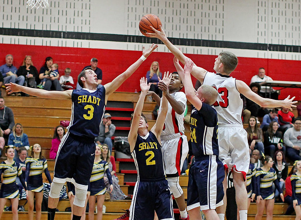 Shady Spring's (3)    and Oak Hill's TJ Wynn (23) jump for a loose ball as other team members scramble during the first quarter of their class AAA sectional basketball game in Oak Hill on Monday. (Chris Jackson/The Register-Herald)