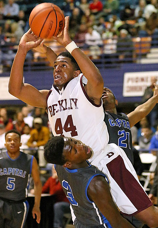 (Brad Davis/The Register-Herald) <br /> Woodrow Wilson's Nequan Carrington crashes into Capital defender Kerry Martin as he tries to drive to the basket during the Flying Eagles' loss to the Cougars Wednesday night at the Beckley-Raleigh County Convention Center.