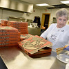 Brad Davis/The Register-Herald<br /> Volunteer Lucy Terry prepares plates of pizza as she works in the kitchen during Little Ceasars Love Kitchen's visit to Fishes & Loaves behind the Church of God Family Worship Center Saturday morning. Little Ceasars provided enough pizza to feed over 1,000 people, with more than 800 attending the event throughout the morning.