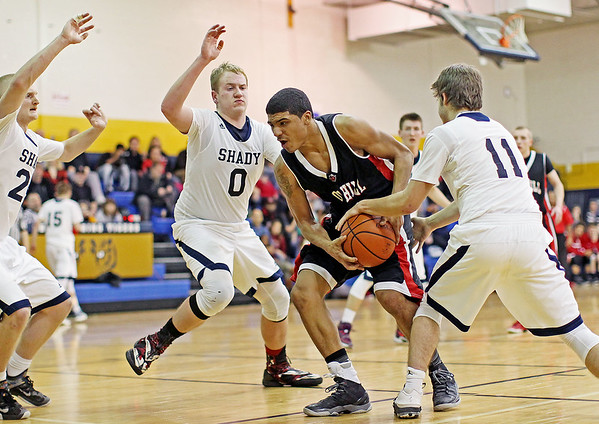 Oak Hill's Deonte Scruggs (5) spins as he drives past three Shady Spring players during their basketball game Tuesday in Shady Spring.