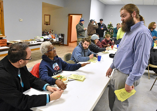 Brad Davis/The Register-Herald<br /> Brandon Richardson (right), founder of Headwaters Defense, has a conversation with area residents Jason Crouch, far left, and Jean Evansmore (2nd from left) as he hands out printed copies of Fayette County's fracking waste and storage ban to attendees during a celebration of the ordinance's passing Tuesday night at Brethren Fellowship Center in Oak Hill.