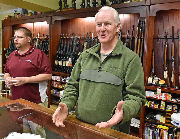 Brad Davis/The Register-Herald<br /> Flat Top Arms owner Ronnie Wood discusses President Barack Obama's executive actions expanding background checks for gun sales as employee Joey Thomas, left, looks on during a Register-Herald visit to the Eisenhower Drive business Wednesday afternoon.