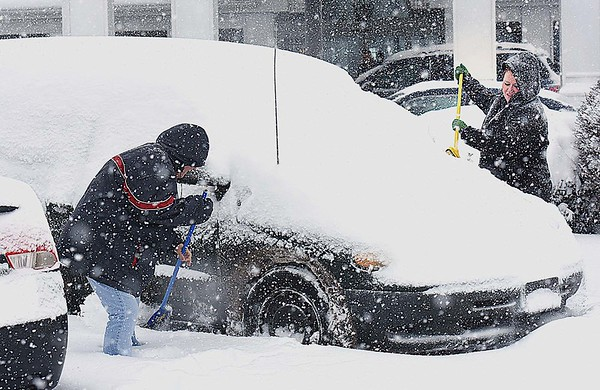 Rick Barbero/The Register-Herald<br /> Cindy Zadora, of Laurel,NC, left, and her daughter, Danielle Zabora, of Rochester, Ny, clean snow off their car on the parking lot of Country Inn & Suites on Harper Road in Beckley Saturday morning.