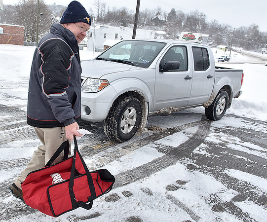 Brad Davis/The Register-Herald<br /> Papa John's delivery driver Brent Varney makes his way to his vehicle with more pizzas as he prepares for another snowy trek Saturday afternoon at the chain's Robert C. Byrd Drive location. Slick, snowy roads were no deterrent for Varney, who said driving around on them was more fun than it looked.