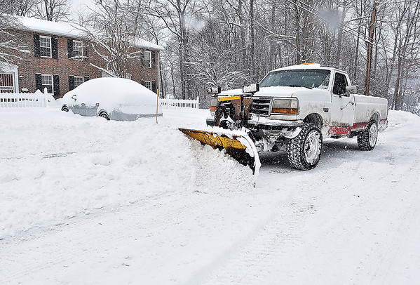 Brad Davis/The Register-Herald<br /> Good sumaritan Garret Tomlin clears access for residents' cars at an apartment complex on Maxwell Hill Road Saturday.