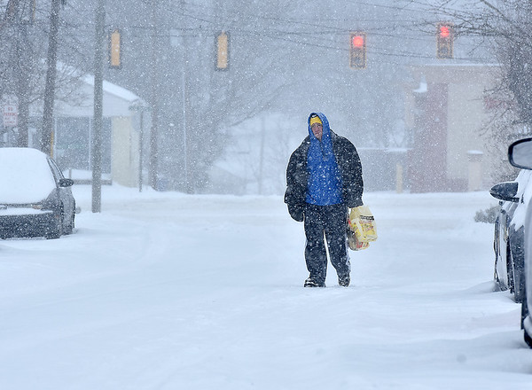 Brad Davis/The Register-Herald<br /> Beckley residentDarren Dunford trudges along 4th Street in whiteout snowfall conditions on his way home from the store Friday afternoon.
