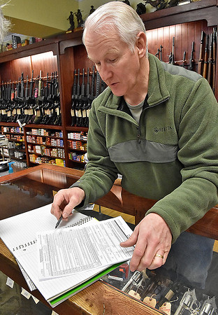 Brad Davis/The Register-Herald<br /> Flat Top Arms owner Ronnie Wood shows the current form one receives to intitiate a backgroud check on firearms purchases as he discusses President Barack Obama's executive actions during a Register-Herald visit to the Eisenhower Drive business Wednesday afternoon.