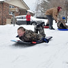 Brad Davis/The Register-Herald<br /> Nine-year-old Cameron Cox makes himself as aerodynamic as possible as he speeds head-first down a perfectly snow-covered Junction Street during Friday's snowstorm while his dad David, upper right, helps 6-year-old Ethan Dorsey get going.