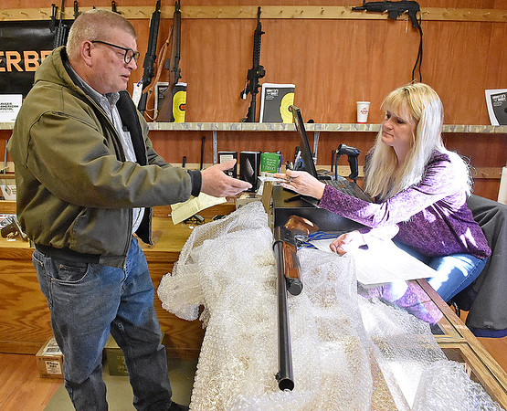 Brad Davis/The Register-Herald<br /> Beaver resident Bill Acord gets his driver's license back from employee Crystal Sizemore as he purchases a 12-gauge Remington Model 11 shotgun at Shooter's Roost on Kanawha Street Wednesday afternoon.