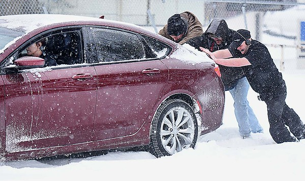 Rick Barbero/The Register-Herald<br /> Aaron Gordon, left, Green Cochran and Derrick Jenkins, help push Stephanie Taylor's vehicle into the KFC parking lot after getting stuck on Robert C Byrd Drive in Beckley Friday morning.
